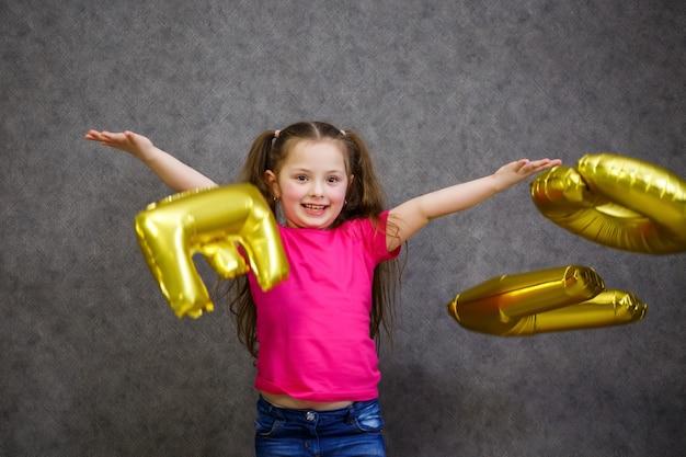 Kleines mädchen im rosa t-shirt spielt mit luftballons