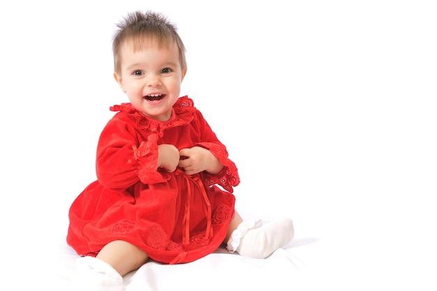 Kleines mädchen im roten kleid, das auf einem bett sitzt