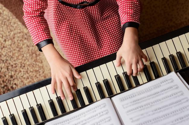 Kleines mädchen im roten kleid, das klassische musik durchführt
