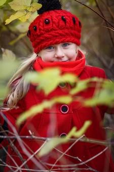 Kleines mädchen im roten mantel und in einem roten hut