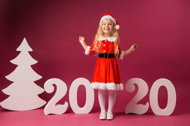 Kleines mädchen im sankt-kostüm steht mit nr. 2020