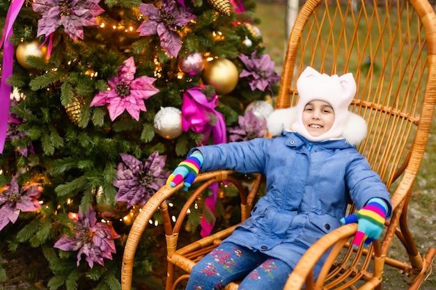 Kleines mädchen im schaukelstuhl in der nähe des weihnachtsbaums auf der straße