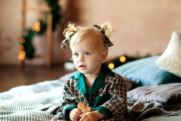 Kleines mädchen im schlafanzug, der lebkuchen isst