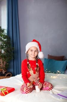 Kleines mädchen im schlafanzug sitzt mit milch und weihnachtsplätzchen