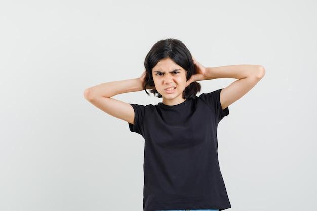 Kleines mädchen im schwarzen t-shirt, das hände auf haar hält und unzufriedenheit, vorderansicht schaut.