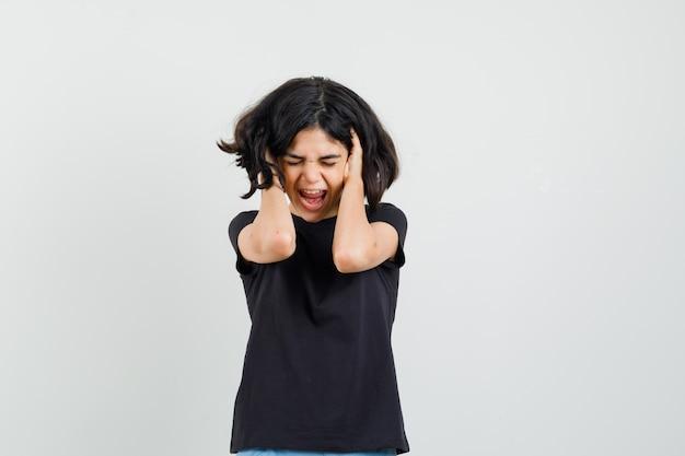 Kleines mädchen im schwarzen t-shirt, das hände im haar hält und gereizt sieht, vorderansicht.