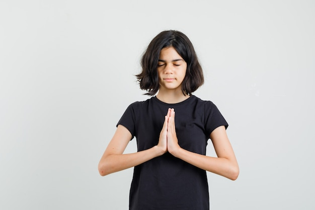 Kleines mädchen im schwarzen t-shirt, das namaste geste zeigt und friedlich, vorderansicht schaut.