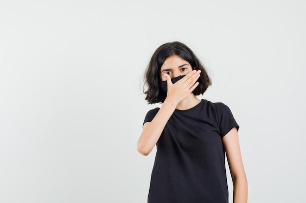 Kleines mädchen im schwarzen t-shirt, maske, die mund mit hand bedeckt, vorderansicht.