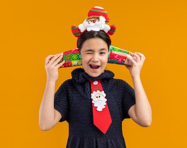 Kleines mädchen im strickkleid, das rote krawatte mit lustigem rand auf kopf hält, der bunte pappbecher über ihren ohren hält und verwirrt fröhlich lächelt