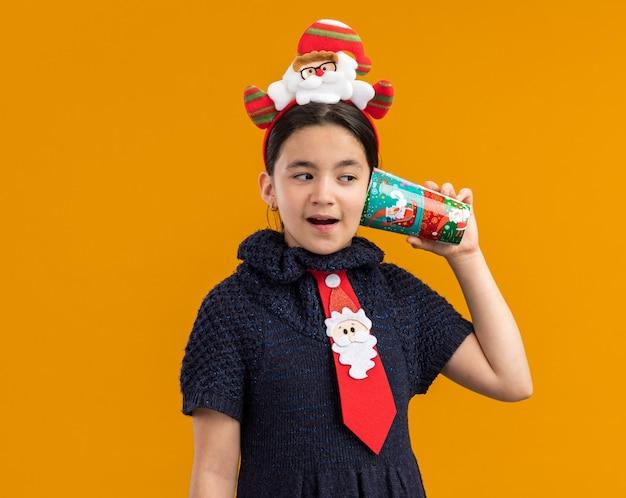Kleines mädchen im strickkleid, das rote krawatte mit lustigem rand auf kopf hält und bunten pappbecher über ihrem ohr hält, das fasziniert schaut