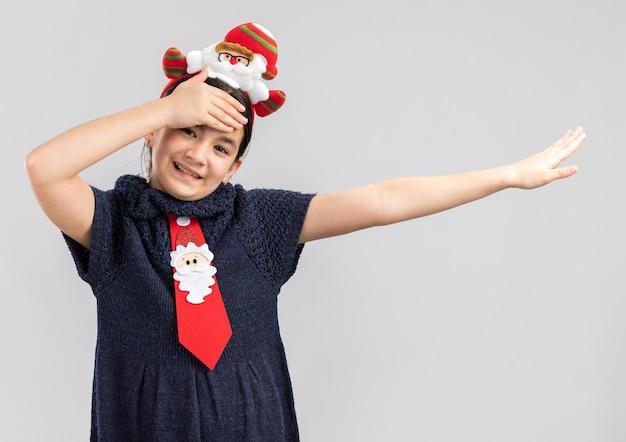 Kleines mädchen im strickkleid, das rote krawatte mit lustigem weihnachtsrand auf kopf glücklich und positiv mit hand auf ihrer stirn trägt, die fröhlich lächelt