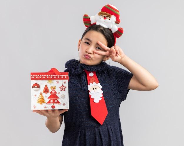 Kleines mädchen im strickkleid, das rote krawatte mit lustigem weihnachtsrand auf kopf hält, der weihnachtsgeschenk glücklich und freudig aussehend zeigt v-zeichen hält