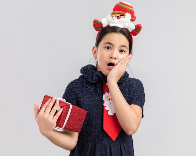 Kleines mädchen im strickkleid, das rote krawatte mit lustigem weihnachtsrand auf kopf hält, der weihnachtsgeschenk hält, das erstaunt und überrascht schaut
