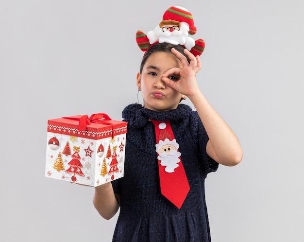 Kleines mädchen im strickkleid, das rote krawatte mit lustigem weihnachtsrand auf kopf hält, der weihnachtsgeschenk hält, das glücklich und positiv schaut durch ok zeichen schaut