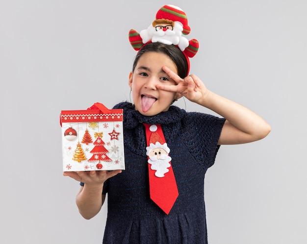 Kleines mädchen im strickkleid, das rote krawatte mit lustigem weihnachtsrand auf kopf hält, der weihnachtsgeschenk hält, das herausstehende zunge schaut, die v-zeichen glücklich und freudig zeigt