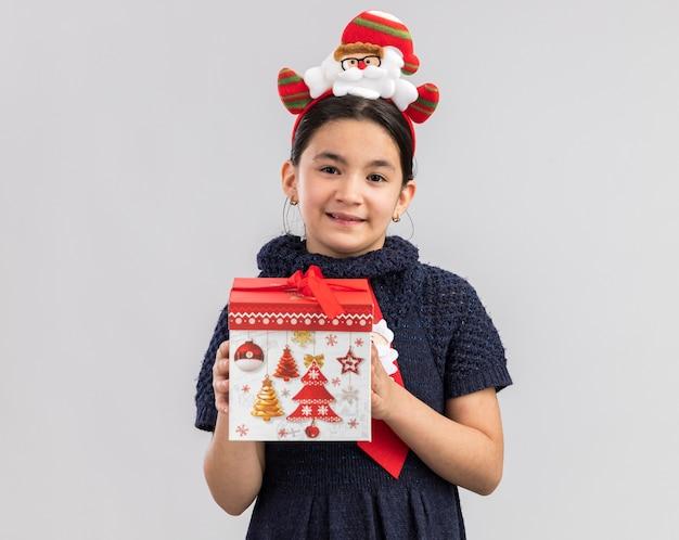 Kleines mädchen im strickkleid, das rote krawatte mit lustigem weihnachtsrand auf kopf hält, der weihnachtsgeschenk hält, das mit lächeln auf gesicht glücklich und positiv schaut