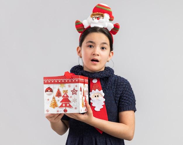 Kleines mädchen im strickkleid, das rote krawatte mit lustigem weihnachtsrand auf kopf hält, der weihnachtsgeschenk hält, das überrascht schaut