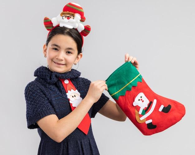 Kleines mädchen im strickkleid, das rote krawatte mit lustigem weihnachtsrand auf kopf hält, der weihnachtsstrumpf hält, der glücklich und positiv lächelt
