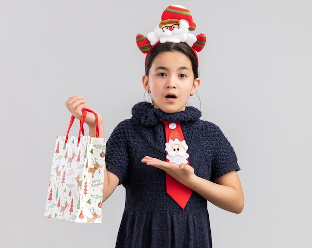 Kleines mädchen im strickkleid, das rote krawatte mit lustigem weihnachtsrand auf kopf hält, die papiertüte mit weihnachtsgeschenk hält, das mit arm der hand präsentiert, die verwirrt schaut