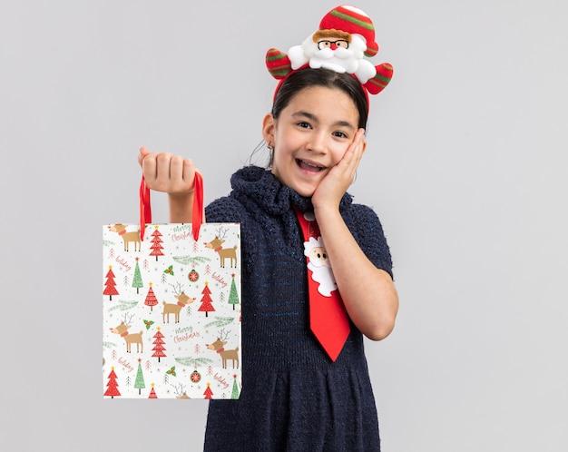 Kleines mädchen im strickkleid, das rote krawatte mit lustigem weihnachtsrand auf kopf hält papiertüte mit weihnachtsgeschenk, das überrascht schaut