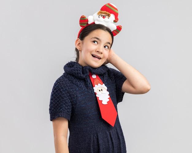 Kleines mädchen im strickkleid, das rote krawatte mit lustigem weihnachtsrand auf kopf trägt und glücklich und positiv schaut