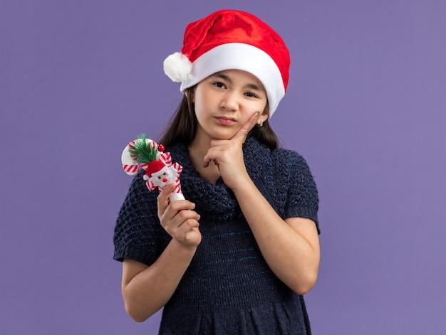 Kleines mädchen im strickkleid, das weihnachtsmütze hält, die weihnachtszuckerstange hält, die mit traurigem ausdruck schaut