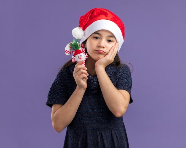 Kleines mädchen im strickkleid, das weihnachtsmütze hält, die weihnachtszuckerstange hält, die mit traurigem ausdruck verwirrt schaut