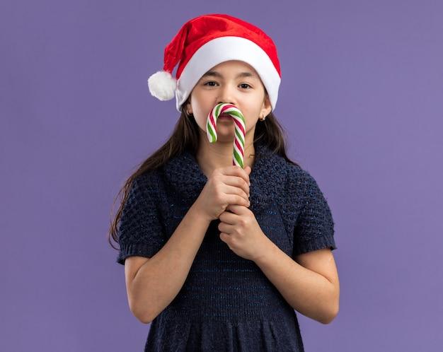 Kleines mädchen im strickkleid, das weihnachtsmütze hält, die zuckerstange hält, die glücklich und positiv lächelnd fröhlich schaut