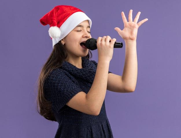 Kleines mädchen im strickkleid, das weihnachtsmütze hält mikrofon singend, das weihnachtsfeier glücklich und positiv feiert