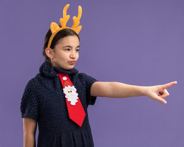Kleines mädchen im strickkleid mit roter krawatte mit lustigem rand mit hirschhörnern auf dem kopf, der beiseite schaut und mit dem zeigefinger auf etwas zeigt