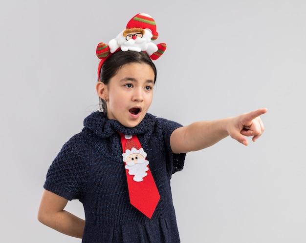 Kleines mädchen im strickkleid mit roter krawatte mit lustigem weihnachtsrand auf dem kopf, der überrascht überrascht mit zeigefinger auf etwas zeigt