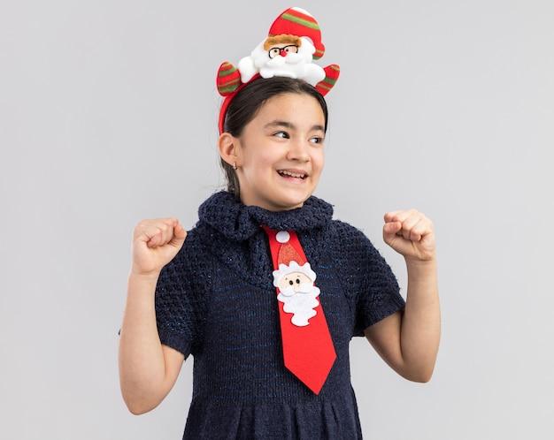 Kleines mädchen im strickkleid mit roter krawatte mit lustigem weihnachtsrand auf geballten fäusten glücklich und aufgeregt