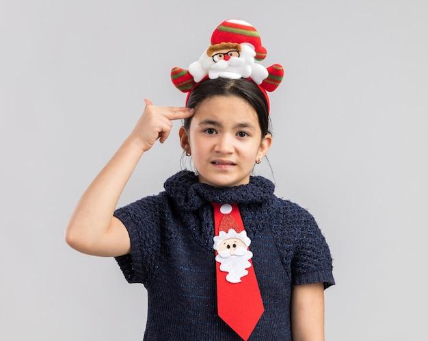 Kleines mädchen im strickkleid trägt rote krawatte mit lustigem weihnachtsrand auf kopf, der genervt pistolengeste mit fingern über kopf macht