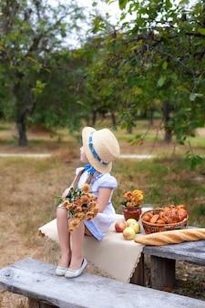 Kleines mädchen im strohhut mit blumenstrauß sitzt auf bank auf picknick im garten. sommerurlaub.