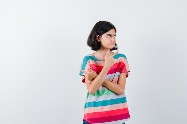 Kleines mädchen im t-shirt, das auf die obere rechte ecke zeigt und nachdenklich aussieht, vorderansicht.