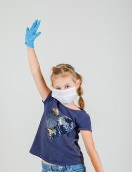 Kleines mädchen im t-shirt, in den handschuhen und in der maske, die großes zeichen mit händen, vorderansicht zeigen.