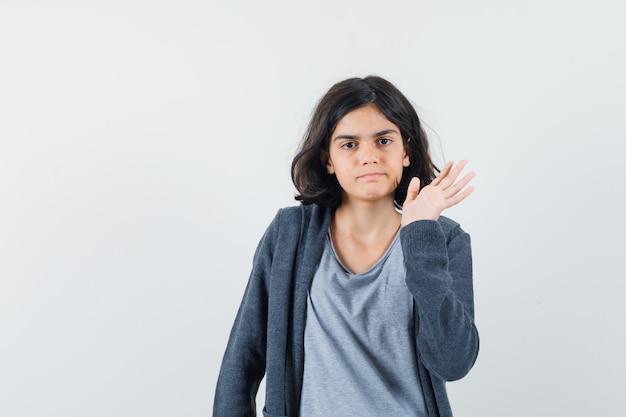 Kleines mädchen im t-shirt, jacke, die hand winkt und selbstbewusst aussieht, vorderansicht.