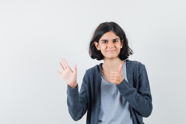 Kleines mädchen im t-shirt, jacke, die hand winkt, zeigt daumen hoch und schaut fröhlich, vorderansicht.