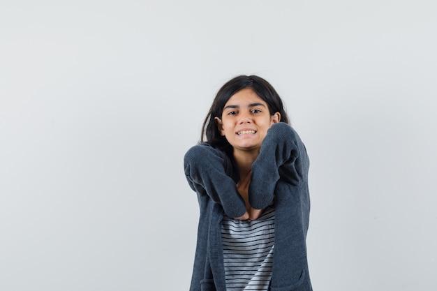 Kleines mädchen im t-shirt, jacke, die ihre ellbogen streckt und entspannt aussieht