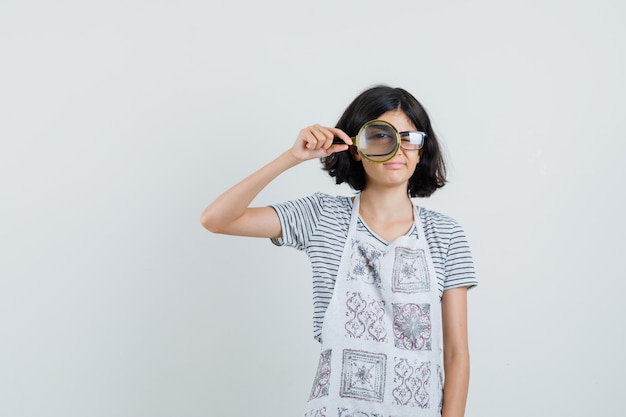 Kleines mädchen im t-shirt, schürze, die durch lupe schaut und vernünftig schaut,