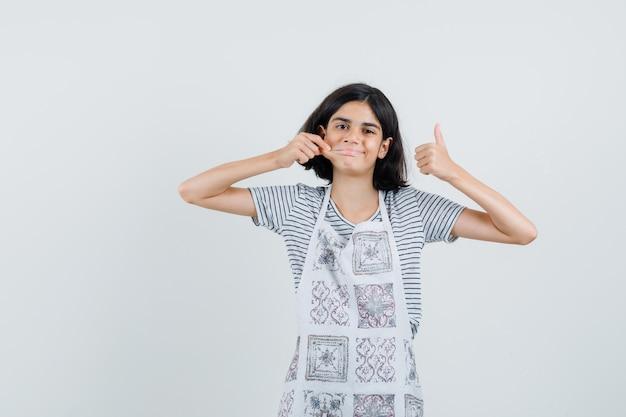 Kleines mädchen im t-shirt, schürze zieht ihre wange, zeigt daumen hoch,