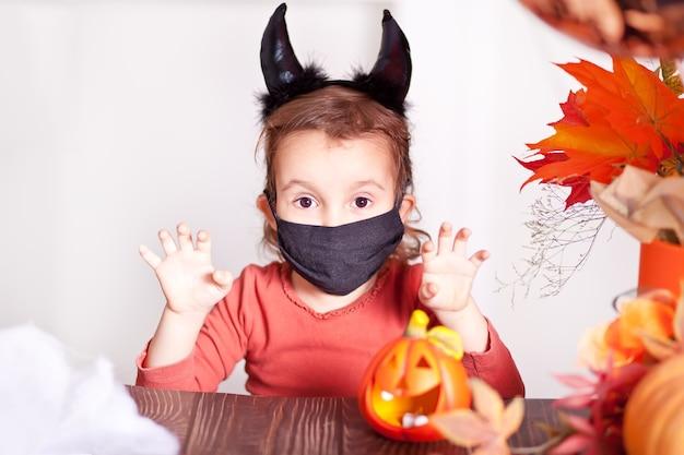 Kleines mädchen im teufelskostüm für halloween