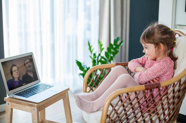Kleines mädchen im video-chat mit ihren großeltern mit laptop