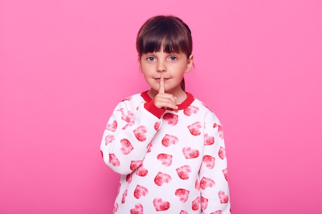 Kleines mädchen im vorschulalter, legt ihren finger in die nähe ihrer lippen, kleidet sich in pullover, isoliert über rosa wand.
