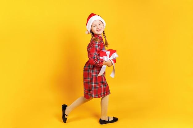 Kleines mädchen im weihnachtsmann-hut schleicht mit weihnachtsgeschenk.