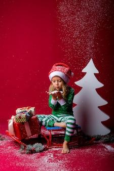 Kleines mädchen im weihnachtspyjama oder im elfenkostüm und in der weihnachtsmannmütze fängt den schnee, der auf einem schlitten sitzt