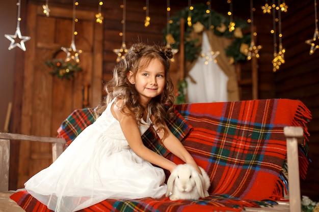 Kleines mädchen im weißen kleid, das auf der bank mit weißem kaninchen sitzt