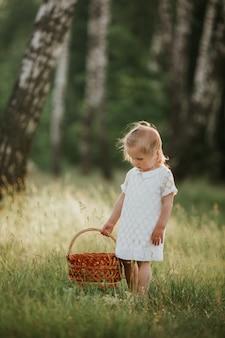 Kleines mädchen im weißen kleid mit korb sonnigen sommertag im wald genießend