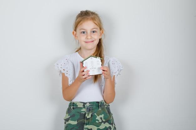Kleines mädchen im weißen t-shirt, rock, der hausmodell hält und glücklich schaut