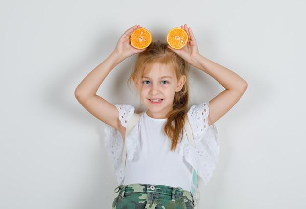 Kleines mädchen im weißen t-shirt, rock, der orangen auf kopf hält und froh aussieht